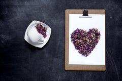 Klembord met en een hart van bloemen op zwarte achtergrond Valen Stock Fotografie