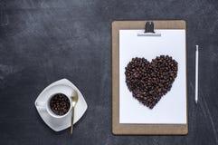 Klembord met en een hart van koffie op zwarte achtergrond Valent Royalty-vrije Stock Afbeelding
