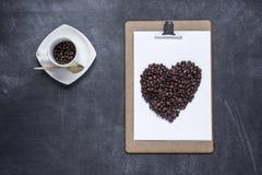 Klembord met en een hart van koffie op zwarte achtergrond Valent Royalty-vrije Stock Fotografie