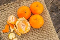 Klementinen auf einer Jutefaserbasis mit einem Holztisch Lizenzfreies Stockbild