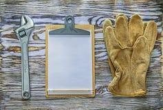 Klemmbrett des justierbaren Schlüssels der Schutzhandschuhe auf hölzernem Brett Lizenzfreies Stockfoto