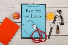 Klemmbrett mit Text u. x22; Tschüss cellulite& x22; , Buch, Brillen, Uhr, Frucht und Stethoskop stockfoto
