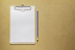 Klemmbrett mit Weißbuch und Bleistift auf Holztisch Stockfoto