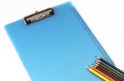 Klemmbrett und bunte Bleistifte lokalisiert auf weißem Hintergrund Lizenzfreies Stockbild
