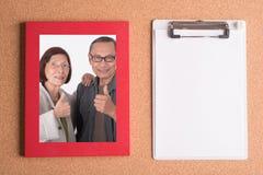 Klemmbrett und Rahmen mit Bild von älteren Paaren auf hölzernem Vorsprung Lizenzfreies Stockfoto