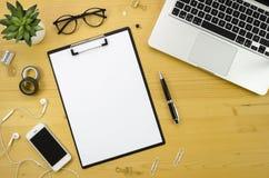Klemmbrettmodell Hauptschreibtischarbeitsplatz mit mit silbernem Notizbuch-, Smartphone- und Bürozubehör auf hölzernem Schreibtis Lizenzfreie Stockfotografie