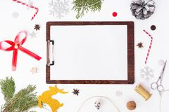 Klemmbrettweihnachtszusammensetzung Tannenzweige, Kegel und Weihnachtsdekorationen auf weißem Hintergrund Draufsicht der flachen  Stockfoto