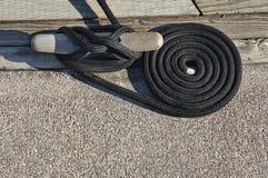 Klemme und aufgerolltes Seil des Schwarzen am Dock. Stockfotos