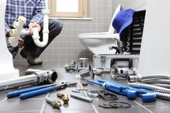 Klempner bei der Arbeit in einem Badezimmer, Reparaturservice plombierend, bauen zusammen Lizenzfreies Stockbild