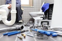 Klempner bei der Arbeit in einem Badezimmer, Reparaturservice plombierend, bauen zusammen Stockbilder