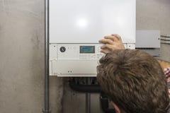 Klempner, der die Wartung eines kondensierenden Kessels durchführt lizenzfreies stockbild