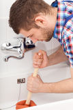 Klempner, der einen bathtube Abfluss freimacht Lizenzfreie Stockfotografie