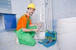 Klempner, der im Badezimmer arbeitet Lizenzfreies Stockbild
