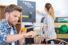 Klempner, der Metallsäge verwendet, um Rohre zu verringern Lizenzfreie Stockfotografie