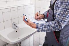 Klempner, der vor Waschbeckenschreiben auf Klemmbrett steht Lizenzfreie Stockfotos