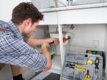 Klempner-Fixing Sink In-Küche Stockfotografie