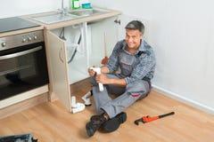 Klempner Repairing Sink Pipe in der Küche stockfoto
