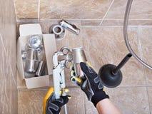 Klempner repariert Wannenfalle im Badezimmer Stockfotografie