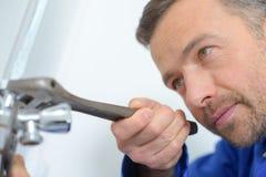 Klempner stark bei der Arbeit über Job Lizenzfreie Stockfotos