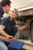 Klempner-unterrichtender Lehrling, zum der Küche-Wanne zu reparieren lizenzfreies stockbild