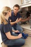 Klempner-unterrichtender Lehrling, zum der Küche-Wanne zu reparieren Stockfoto