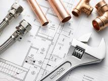 Klempnerarbeit-Ausrüstung auf Haus-Plänen Lizenzfreies Stockfoto
