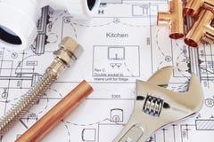 Klempnerarbeit-Hilfsmittel angeordnet auf Haus-Plänen Stockfotografie