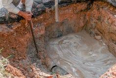 Klempnerarbeit-Instandsetzer Arbeitskräfte, die graben, um Wasserleitungen zu reparieren lizenzfreies stockfoto