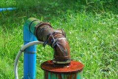 Klempnerarbeitoberrohr und -wasser leckt, Stahlrost des alten Hahnrohres auf Grasboden Lizenzfreie Stockbilder