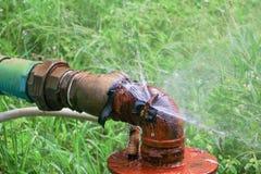 Klempnerarbeitoberrohr und -wasser leckt, Stahlrost des alten Hahnrohres auf Grasboden Lizenzfreies Stockfoto