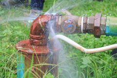 Klempnerarbeitoberrohr und -wasser leckt, Stahlrost des alten Hahnrohres auf Grasboden Lizenzfreie Stockfotografie