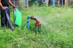 Klempnerarbeitoberrohr und -wasser leckt, Stahlrost des alten Hahnrohres auf Grasboden Stockfotos