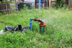 Klempnerarbeitoberrohr und -wasser leckt, Stahlrost des alten Hahnrohres auf Grasboden Lizenzfreies Stockbild