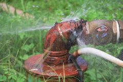 Klempnerarbeitoberrohr und -wasser leckt, Stahlrost des alten Hahnrohres auf Grasboden Stockfoto