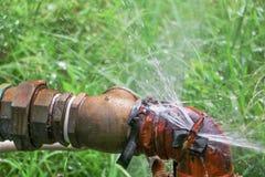 Klempnerarbeitoberrohr und -wasser leckt, Stahlrost des alten Hahnrohres auf Grasboden Stockbilder