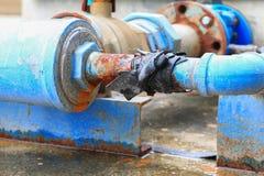 Klempnerarbeitrohr und -wasser leckt, industrielles altes Hahnrohr des Stahlrosts Stockfotografie