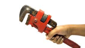 Klempnerarbeitschlüssel in der männlichen Hand auf lokalisiert Stockfotografie