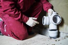 Klempnerarbeitskraft, die Abwasserleitungen in Kanalisationssystem installiert Stockfoto