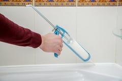 Klempnerhand, die Silikondichtungsmittel im Badezimmer anwendet Lizenzfreies Stockfoto