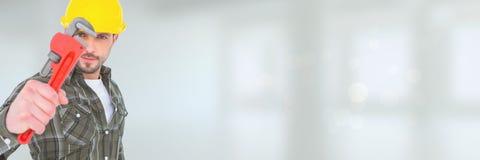 Klempnermann, der einen Schlüssel gegen weißen Hintergrund mit Aufflackern hält Lizenzfreie Stockbilder