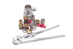 Klempnerschlüssel und -mehrere Klempnerarbeitkomponenten auf einem hellen backgr Stockbild