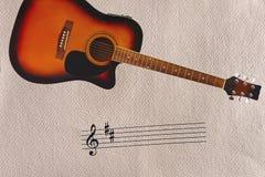Klepka i akustyczna sunburst gitara przy wierzchołkiem szorstki kartonowy tło Fotografia Royalty Free