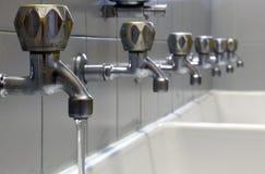 Klepnięcie z wodą, wiele klepnięcia zamykający i biały ceramiczny washbasin fotografia royalty free