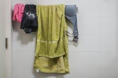 Kleren, brassière en groene handdoek bij het hangen van rek in badkamers royalty-vrije stock afbeelding