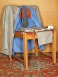 Kleren die op een oude stoel hangen Royalty-vrije Stock Foto's