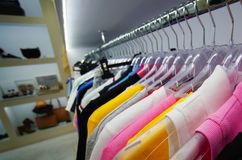 kleren die op hangers in de opslag hangen royalty-vrije stock afbeelding