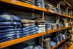 Kleren op opslagplank bij een kledingsafdeling Stock Afbeeldingen