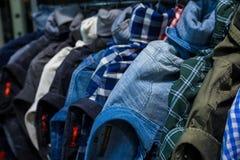 Kleren op opslagplank bij een kledingsafdeling Stock Fotografie