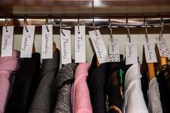 Kleren tegen dagen in garderobe worden gesorteerd die stock foto
