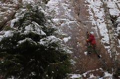 Kletterer auf einem Felsen in einem Winterwald lizenzfreie stockfotografie